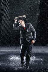 Businessman covering head with binder, running through rain