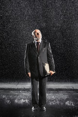 Rain falling on businessman Without Protection, looking to sky
