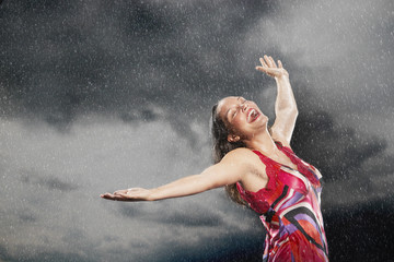 Woman, arms outstretched, smiling, standing in rain