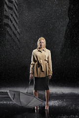 Woman standing in rain, not Using Her Umbrella