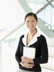 Smiling businesswoman standing, holding notebook