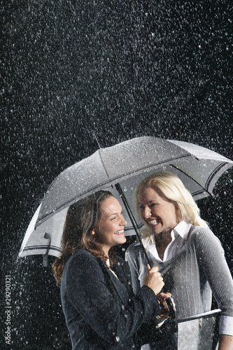 Smiling Businesswomen Standing Under Umbrella together during rain
