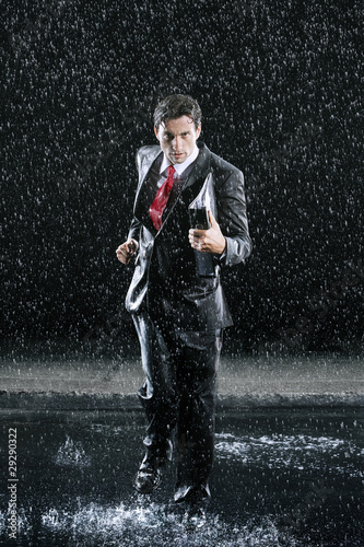 Businessman holding binder, running in Rain