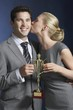 Woman kissing man holding trophy against dark background