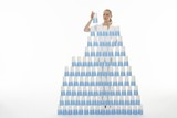 Woman stacking plastic cups into pyramid against white background