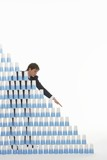 Man stacking plastic cups into a pyramid against white background
