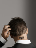 Young man with bar code tattoo on his neck, scratching head, back view