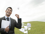 Laughing business man on grass field throwing litter behind