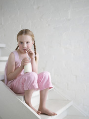 Barefoot Girl Drinking Glass of Milk, sitting on stairs