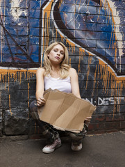Young woman squatting by brick wall, pretending begging