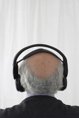 Senior man wearing head phones in studio, head and shoulders, back view