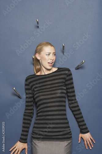Woman surrounded by thrown knives against blue background