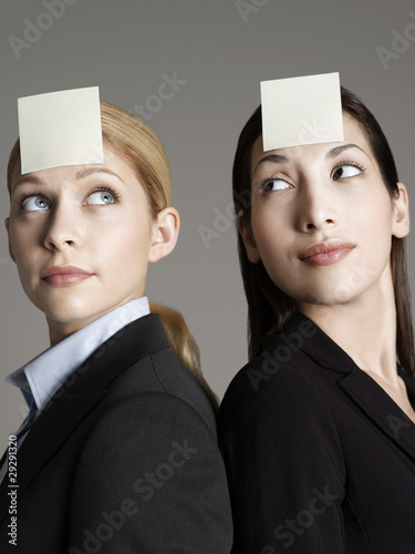 Portrait of two female office workers with sticky notes on forehead