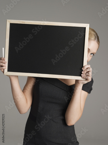 Portrait of young female teacher peeking from behind blackboard