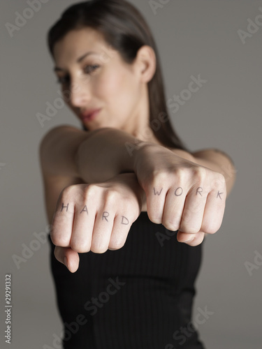 Young woman showing fists with 'hard work text, focus on foreground