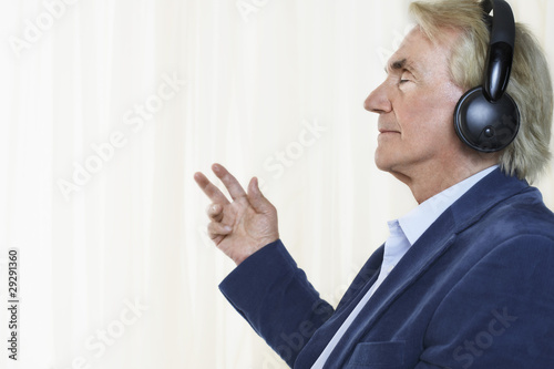 Senior man wearing headphones, profile, in studio