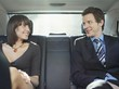 Mid adult woman and businessman talking at back seat of car