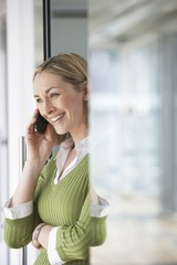 Business woman using mobile phone in office, portrait