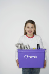 Girl 10-12 holding recycling container, smiling