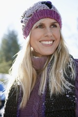 Woman wearing winter clothing, smiling, portrait