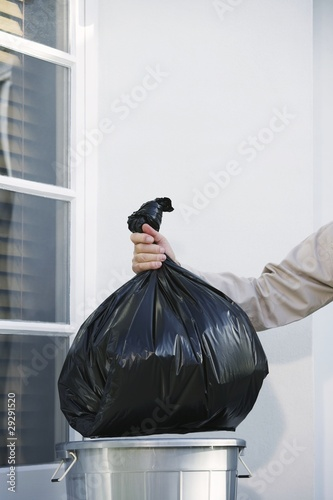 Man Taking Garbage Out of Can