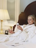 Woman wearing bathrobe using mobile phone, lying on bed