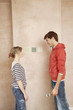 Couple standing face to face, choosing paint colour samples on wall