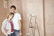 Couple standing, embracing in unrenovated room, portrait