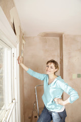 Woman standing in unrenovated room with scraping tool in hand