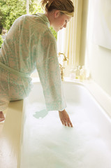 Woman in bathrobe bending down over bathtub filled with bubbles, testing water, back view