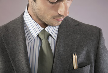 Young businessman with pencils in pocket, portrait