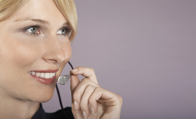 Businesswoman wearing headset, close-up, portrait