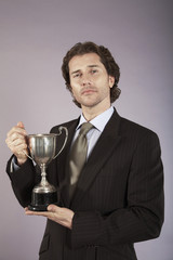 Businessman holding trophy, portrait