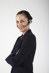 Businesswoman wearing wireless headset, on white background, portrait