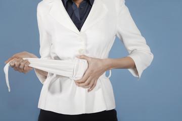Businesswoman adjusting belt, mid section