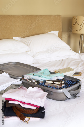 Stacks of folded clothes and packed Suitcase on Bed