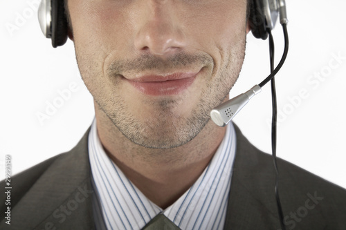 Businessman wearing headset, close-up, portrait