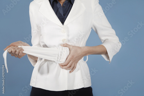 Businesswoman adjusting belt, mid section