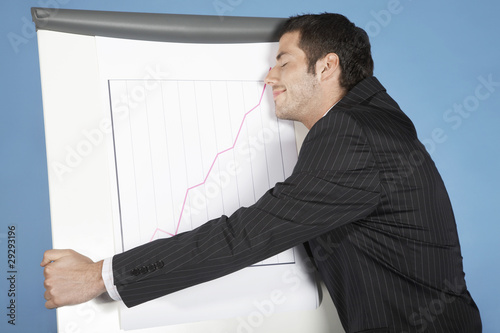 Businessman hugging line graph showing success