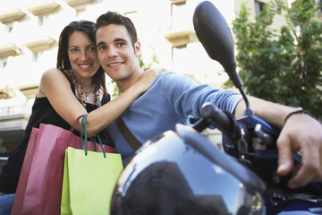 Young couple on motor scooter with shopping bags, portrait