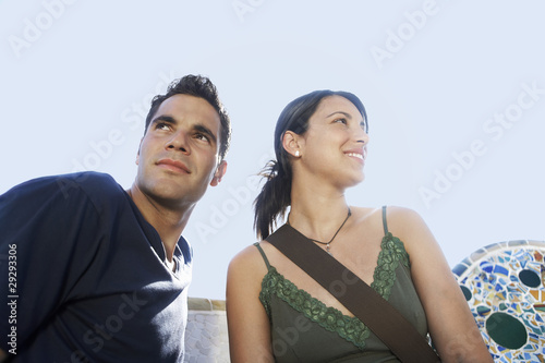 Young couple sitting on stone bench, portrait
