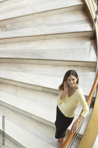 Woman standing on staircase, using mobile phone, elevated view.