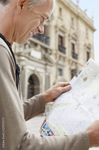 Tourist on Granada street Reading Map, side view