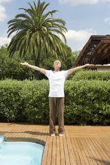 Middle-aged man standing by swimming pool with arms outstretched doing tai chi