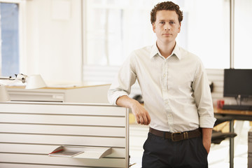 Mid-adult male office worker standing by cubicle, portrait