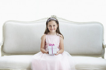 Smiling girl in tutu sitting on sofa holding gift, portrait