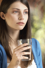 Young woman drinking glass of water, portrait