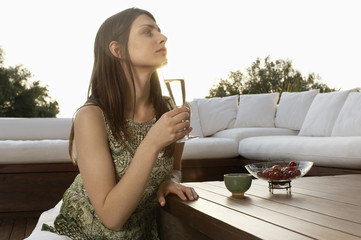 Young woman drinking champagne and eating fruit, portrait