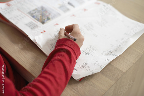 Girl doing homework on table, close up of hand on exercise book