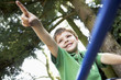 Young Boy sitting on monkey bars pointing, close up